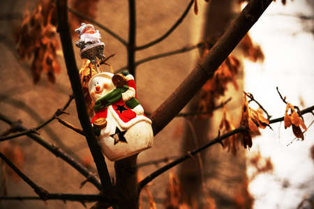 Joyful snowman toy hanging on tree with brown seeds