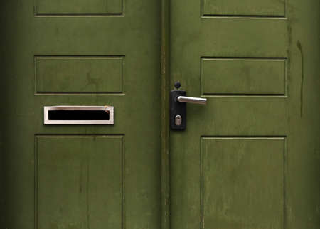 Green wooden entrance door with mailbox hole and metal handle Stock Photo