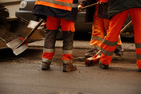 Road works with men in uniform working with shovel and broom Stock Photo