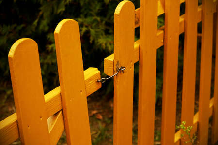 Yellow wooden plank garden fence with metal hook