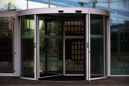 Turning round door entrance into a modern glass building with reflections