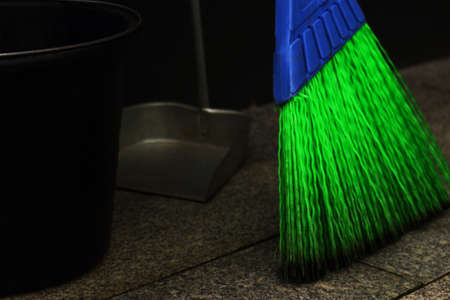 Bright blue and green synthetic street mop with black bucket and a scoop close up Foto de archivo - 134568977