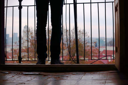 Man in jeans standing on balcony view on old town from tiled floor ground in autumn
