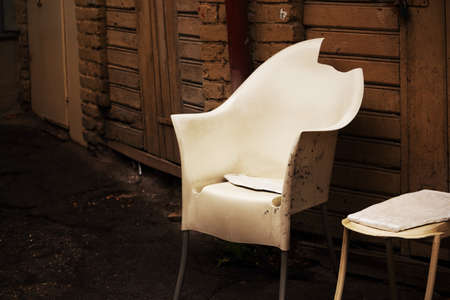 White broken plastic armchair in yard on wooden wall with doors backgrund