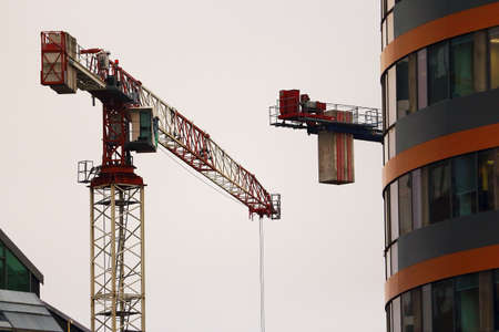 Construction cranes working on modern building on white sky background