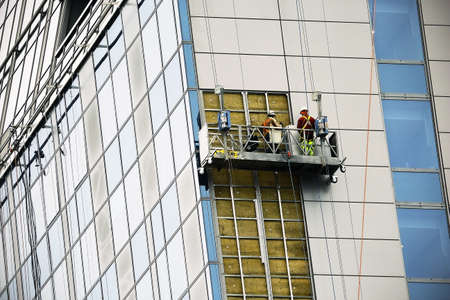 Men working on construction site lift building modern glass structure