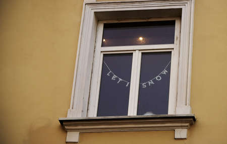 White frame window in old town building with christmas writing hanging decoration Stock Photo