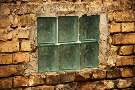 Thick glass selfmade window in old brick wall fixed by cement
