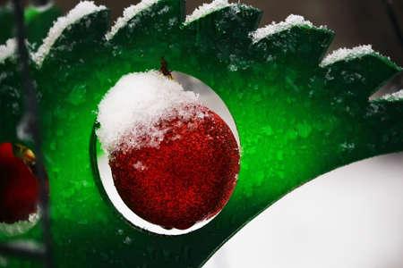 Roter Weihnachtsdekorationsball, der auf grünem Plastikweihnachtsbaumzweig übergibt