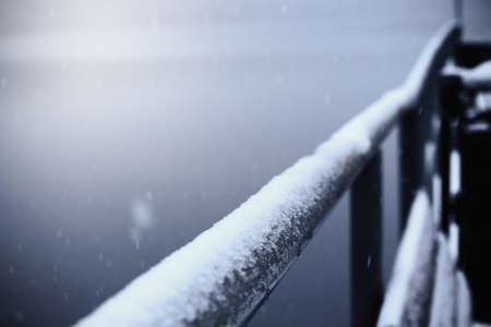 Metal handrail in snow with falling snowflakes in blue shade