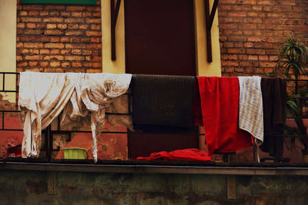 Clothes and rug hanging and drying on a rope on red brick wall building facade bakground with brown door