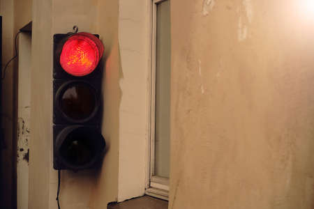 Old street traffic light with glowing red light hanging on wall near a window