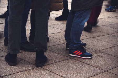 Mens legs with footwear standing on pavement in jeans in crowd Stock Photo