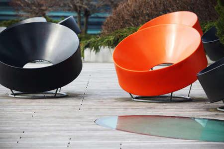 Round black and orange modern chairs standing outdoors in the sun