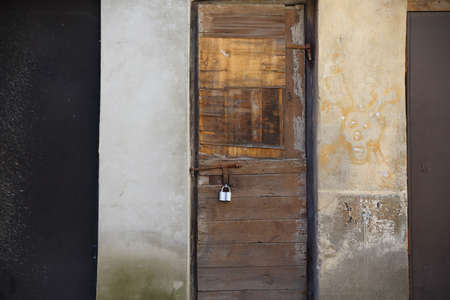 Old weathered locked wooden door with padlock in old building