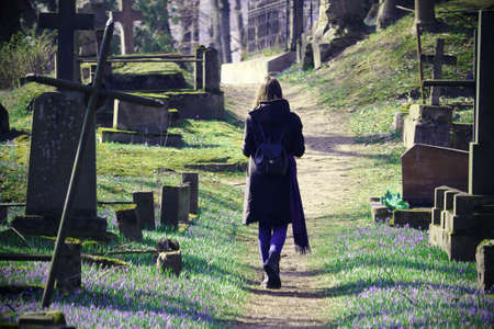 Young woman walking on cemetery path between grave stones and crosses in spring on sunny day Standard-Bild - 143774101