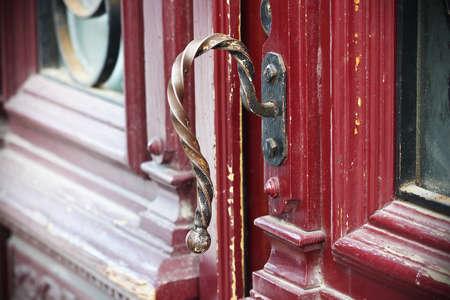 Gilded iron croocked door handle on red painted wooden door with glass details