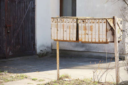 Old white rusty mail boxes in empty yard on sunny day
