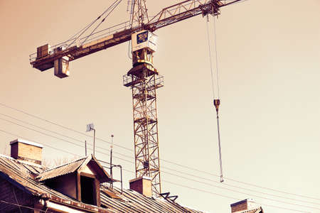 Industrial construction site crane standing above old house roof sepia tone filter