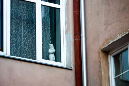 White frame window in old town building with women statue and lace curtains with visible rusty water drain pipe Stock Photo