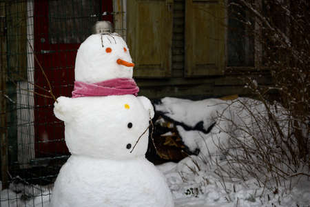 Snowman with carrot nose and red scarf standing near house 版權商用圖片