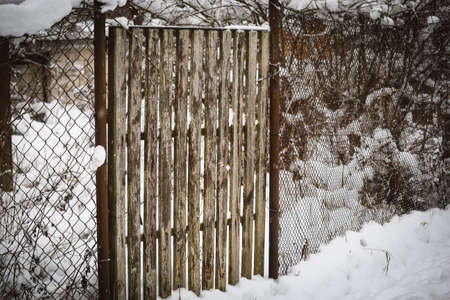 Small wooden plank entrance gate in winter with wire fence