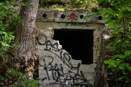 Vilnius, Lithuania - 07062020: Hidden catacomb with wall art graffiti writings in forest