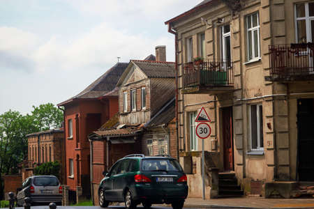 Vilnius, Lithuania - 11062020: Cars on road drive near old buildings on old town street 新聞圖片