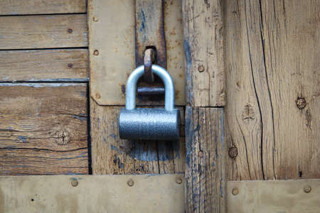 Metal padlock hanging on locked wooden door