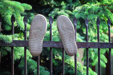 Two sneakers hanging on iron fence on green plant background