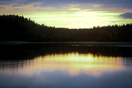 Sunset light over dark forest trees behind lake water with reflections