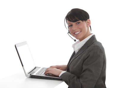 Young business women with headset types on laptop photo