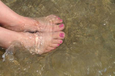 u�as pintadas: los pies desnudos de la mujer en el agua