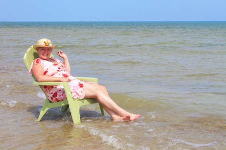 women sitting in adirondak chair in lake cooling off on a hot summers day photo