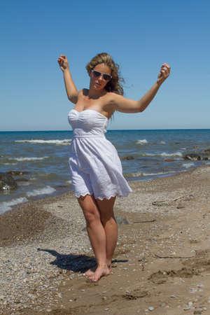 windblown: Women dances on the beach in a happy summer dress