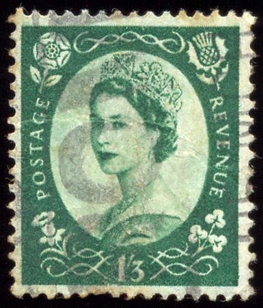 shilling: UNITED KINGDOM - CIRCA 1952 to 1965: An English One Shilling and Three Pence Green Used Postage Stamp showing Portrait of Queen Elizabeth 2nd, circa 1952 to 1965