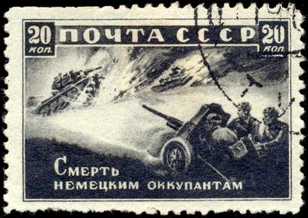 invaders: UNION SOVIETICA - CIRCA 1942: Un sello impreso por la Uni�n Sovi�tica post se titula Muerte a los invasores alemanes !, circa 1942. Muestra los artilleros rusos disparaban contra los tanques fascistas. Editorial
