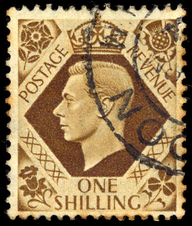 shilling: UNITED KINGDOM - CIRCA 1937 to1947: An English One Shilling Brown Used Postage Stamp showing Portrait of King George VI, circa 1937 to 1947