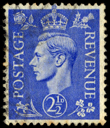 UNITED KINGDOM - CIRCA 1950 to 1952: An English One and a Half Pence Green Used Postage Stamp showing Portrait of King George VI, circa 1950 to 1952 Editorial