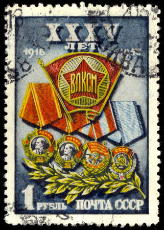 communistic: USSR - CIRCA 1953: A Stamp printed in the USSR shows the Komsomol badge against Lenin two awards, awards of the Red flag and an award of the Labour Red flag-awards of Komsomol, circa 1953