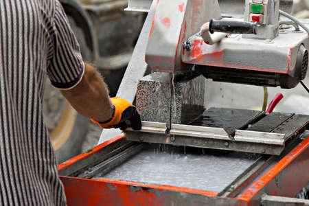 worker and machine cutting a granite block