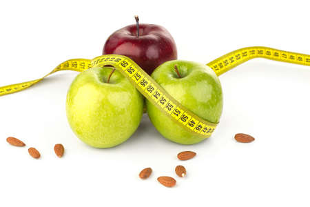 ripe juicy apples, almonds, and tape measure on a white background Stock Photo