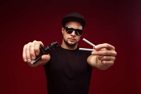 dependencies: Man with cigarettes and e-cigarette on a red background. Choice between dependencies