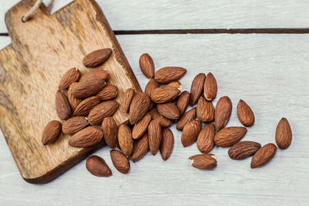 Peeled almonds on a wooden background Stock Photo