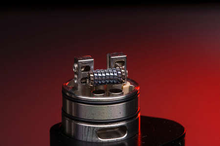 staple staggered fused clapton coil in rebuildable dripping atomizer over dark background