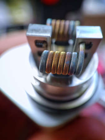 staple staggered fused clapton coil in rebuildable dripping atomizer over color background Banco de Imagens