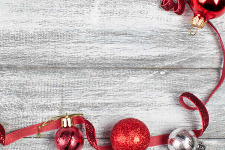 Red ribbon, red and silvery christmas balls on a wooden background Reklamní fotografie - 90841542