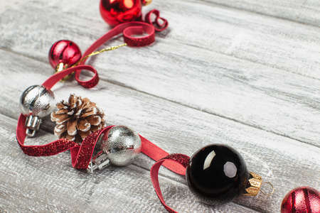 fir cones and red and silvery New Year balls on a wooden background Reklamní fotografie - 90841564