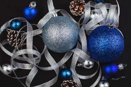 fir cones and blue and silvery New Year balls on a black background
