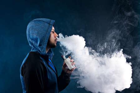 vaping man holding a mod. A cloud of vapor. dark blue background.